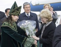 A Kazakh woman adorned in ceremonial dress presents a bouquet of flowers to Lynn Cheney, wife of Vice President Dick Cheney, as they both arrive in Astanta, Kazakhstan, Friday, May 5, 2006